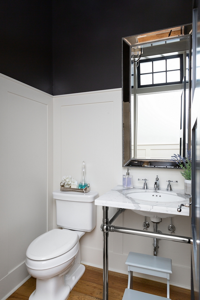 The powder room features a classic marble washstand with metal base and wall paneling #poderroom #paneling #bathroom #wainscotting #washstand