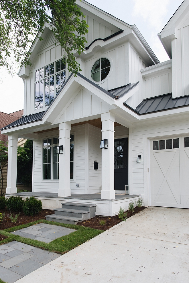 Board and batten home exterior The craftsmanship of this home is evident from every angle The board and batten siding was custom-designed by the builder Also, notice the details above the round window and on the classic porch columns #boardandbatten #roundwindow #pochcolumns #craftsmanship #customsiding #siding