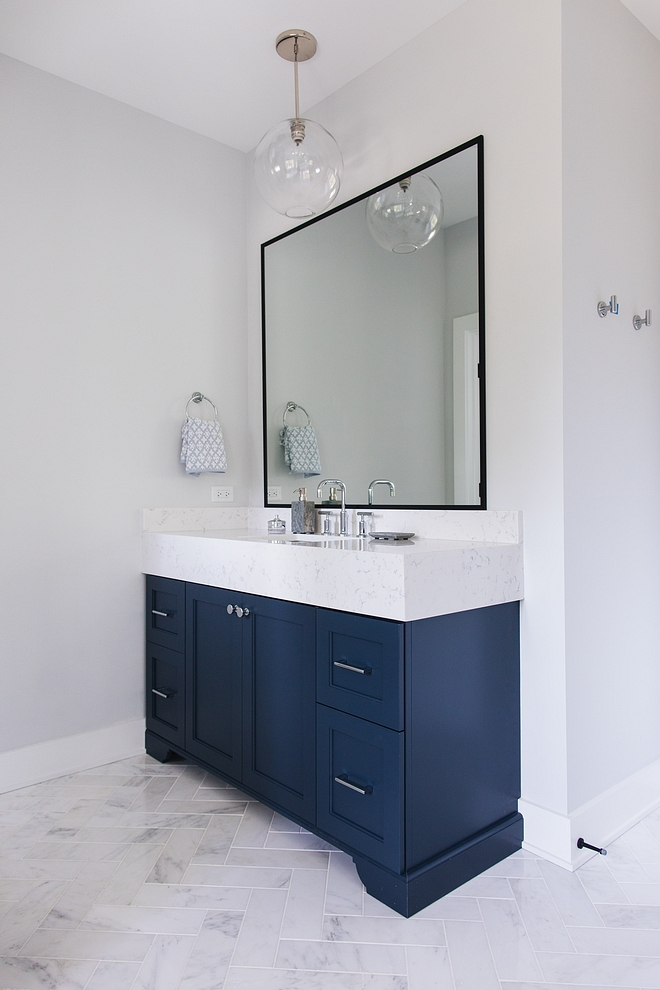 Bathroom with light grey walls painted in Sherwin Williams Site White 7070, navy blue vanities with chunky marble countertop and herringnone floor tile #bathroom #navybluevanity #chunkycountertop