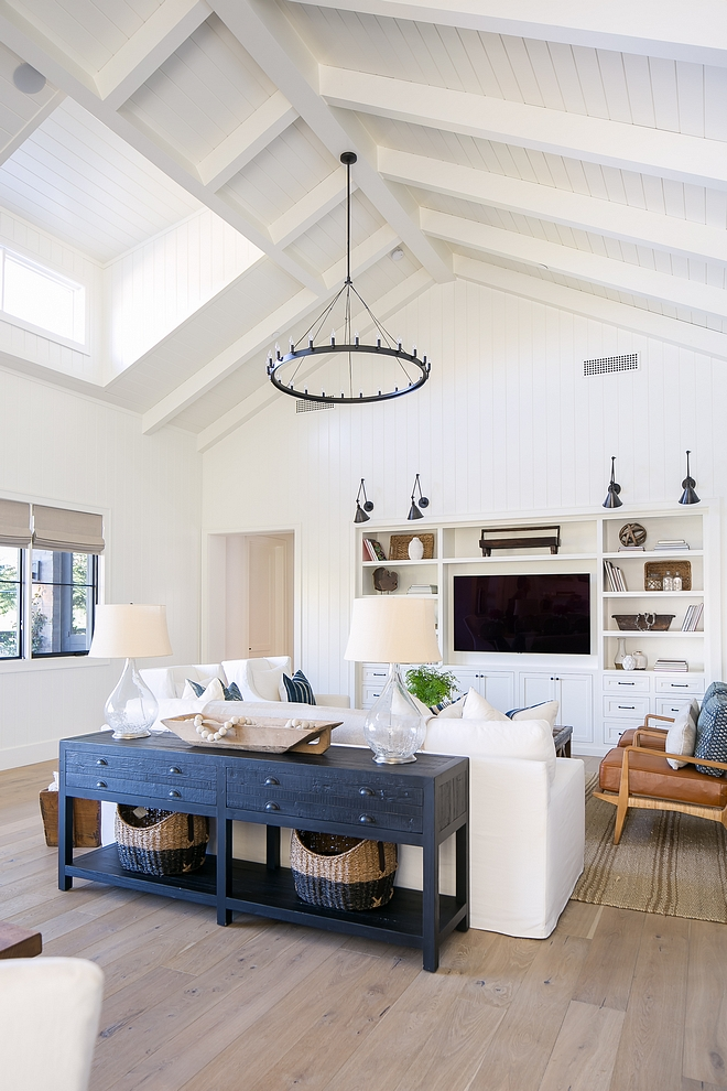 Living room Casual elements such as white shiplap, linen upholstery, swivel chairs and jute rugs, bring a soft and welcoming feel to the entire space #livingroom #shiplap #ceiling #slipcovered #rugs #juterug #casual