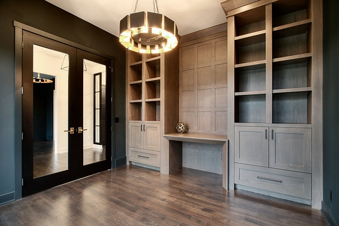 The home office features a pair of custom built-in bookcases flanking a custom desk, which can also used as a console. Notice the grid board and batten paneling