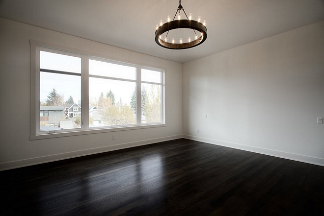 The master bedroom features white walls, painted in Benjamin Moore White Dove OC-17, and dark stained hardwood flooring