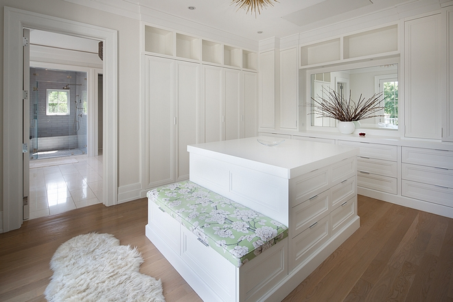 Dressing room Closet with custom cabinetry and island with built-in bench Paint color is Benjamin Moore White #Dressingroom #Closet #cabinetry #closetisland #builtinbench #BenjaminMooreWhite