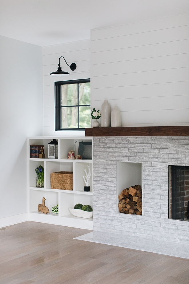 Modern farmhouse Fireplace This modern farmhouse fireplace features a brick-style tile and a dedicated wood storage space Mantel is made of Walnut