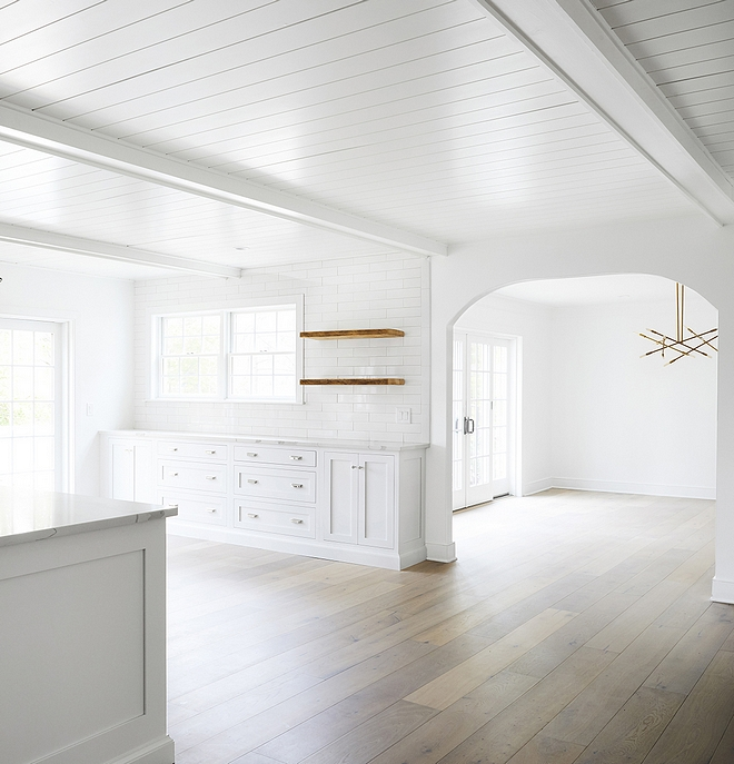 White kitchen with matte hadrwood flooring Ceiling is Tongue and groove with beams painted in Benjamin Moore Chantilly Lace #Whitekitchen #mattehadrwoodflooring #hadrwoodflooring #Ceiling #Tongueandgrooveceiling #beamsceing #paintedbeams #BenjaminMooreChantillyLace