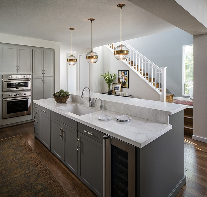 Kitchen island features bar-height counters with Crema Delicato honed marble countertop Sherwin Williams Porpoise #Kitchenisland #SherwinWilliamsPorpoise
