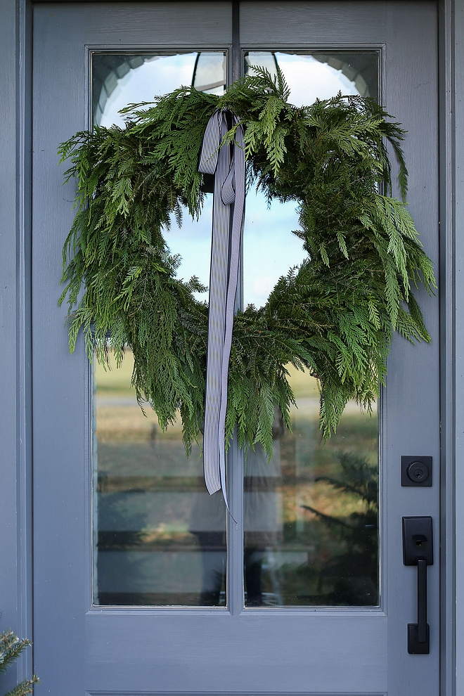 Christmas Decor A natural wreath with a simple stripped ribbon adds a festive yet subtle Christmas feel to the front entry #Christmasdecor #naturalchristmas #naturalchristmasdecor