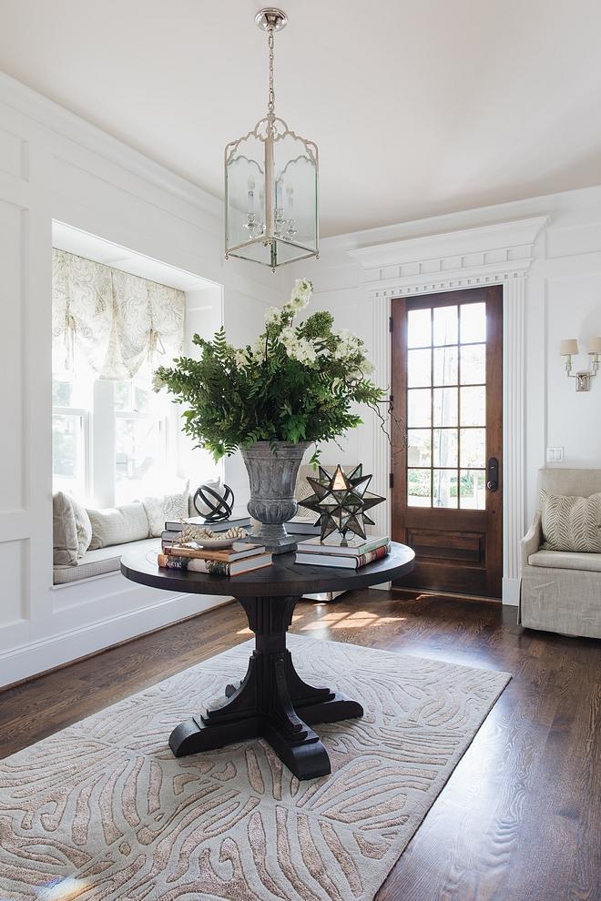 Traditional Foyer Traditional Foyer with round table, rug, window-seat, medium Red Oak Hardwood flooring and Visual Comfort lantern pendant light Traditional Foyer #TraditionalFoyer #traditionalinteriors #foyer