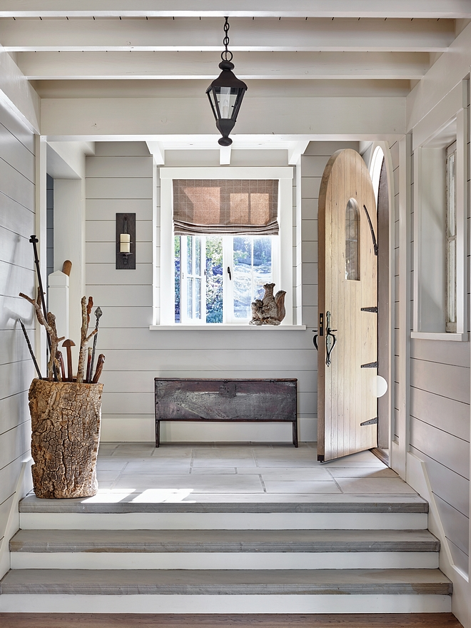 Foyer An enchanting arched door opens to an equally enchanting foyer with natural stone flooring and nickel joint walls shilap #foyer #shiplap #archeddoor #naturalstoneflooring #nickeljointwall #nickeljointshiplap #nickeljointpaneling #nickeljoint
