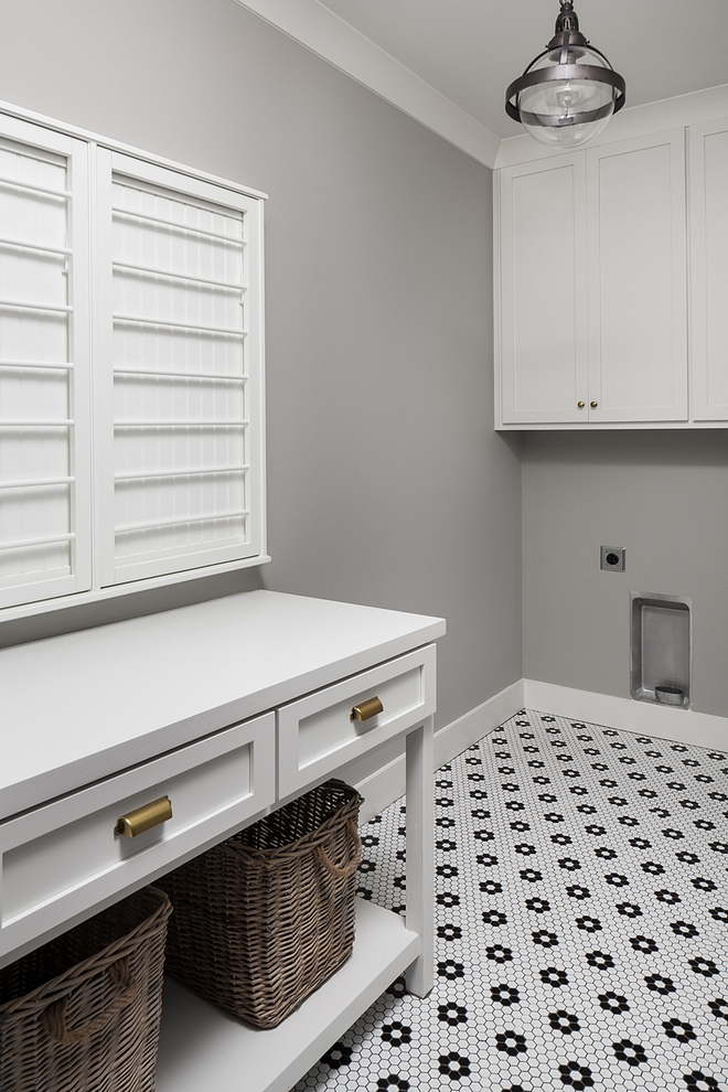 Laundry Room Located upstairs, this laundry room features a custom folding cabinet/island and retro-style mosaic floor tile #LaundryRoom #foldingtable #foldingcabinet #retrotile