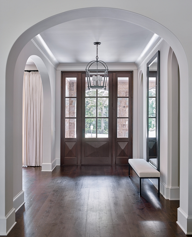 Foyer Featuring elliptical arches, medium-toned hardwood floors and a custom front door, this foyer is impressive and inviting at the same time #foyer #ellipticalarches #arch #hardwoodfloors #frontdoor