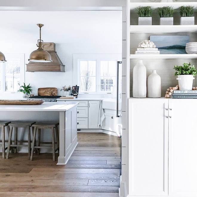 Coastal farmhouse kitchen The living room opens to a large and bright white kitchen with hardwood flooring Notice the beautifully styled bookcase on the right #Coastalfarmhousekitchen #Coastalfarmhouse #kitchen #hardwoodfloors #bookcase