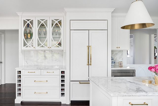 Kitchen Bar Cabinet A paneled refrigerator is flanked by a bar cabinet with eclipse mullion doors and a small cabinet with microwave drawer #kitchen #bar #cabinet #barcabinet #kitchenbar