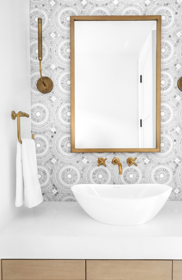 Powder room This powder room was designed to impress! I love the combination of the brass accents with the marble mosaic tile #Powderoom #mosaictile #brass