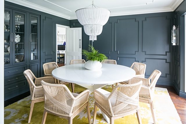 Dramatic dining room with charcoal Gray Wainscotting, white beaded chandelier, modern rope dining chairs and X Base white Round Dining Table #diningroom #darkwainscotting #homedecor #diningtable #xbasediningtable