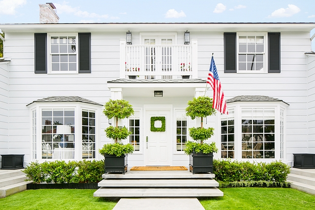 White home exterior with black shutters and black planters by front door Classic curb-appeal #Whitehome #whiteexterior #whiteexteriors #blackshutters #planters #frontdoor #Classiccurbappeal #curbappeal