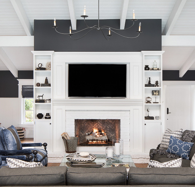 The fireplace at the center of the great room was originally a cream marble. To freshen it up and add a sense of history we added an Italian black Chicago brick in a herringbone pattern, and white painted Chicago brick for the surround and hearth #fireplace #brick #builtins