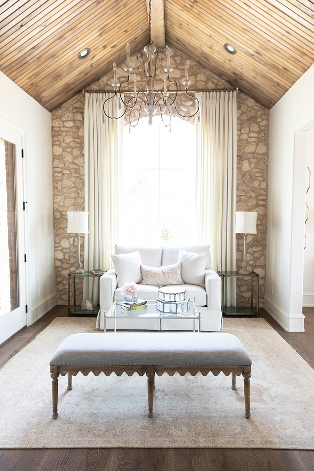 Interior natural stone accent wall Stone is Castlerock stone in a mix of cream and white with white mortar Bedroom sitting room with cathedral vault ceiling and natural stone accent wall Rustic French Interior Design #bedroom #sittingroom #RusticFrench #InteriorDesign #naturalstoneaccentwall