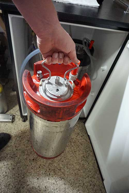 pulling on a keg lid to seal it