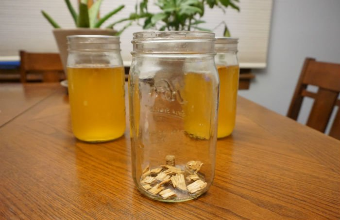 chips of oak wood in the bottom of a glass jar with jars of cider behind it