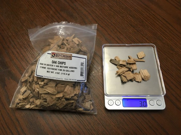 chips of oak wood being weighed on a digital scale before adding them to cider