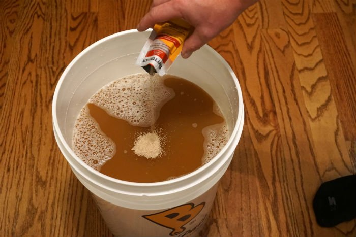 a hand pouring a pack of yeast into a bucket of apple cider
