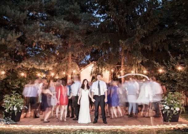 dance floor full of party goers in the backyard at a wedding reception at home with green trees in the evening light