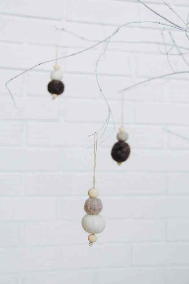 Christmas ornaments made with grey felt and wooden balls hanging on a string displayed on white twigs and a white brick background