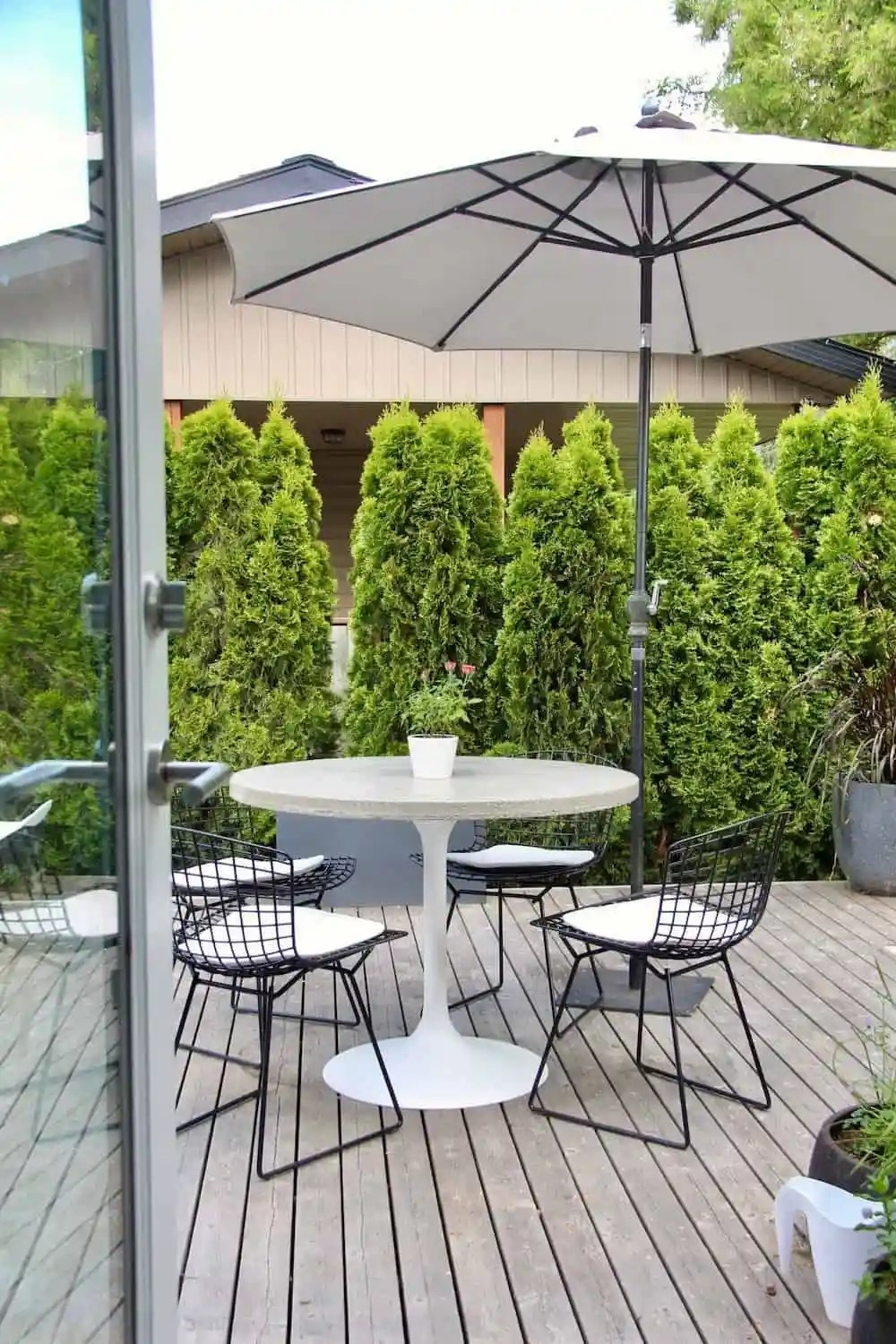 modern patio furniture on grey wooden deck with glass door and umbrella - Concrete Dining Table - A DIY Round Dining Table For Outdoors (or