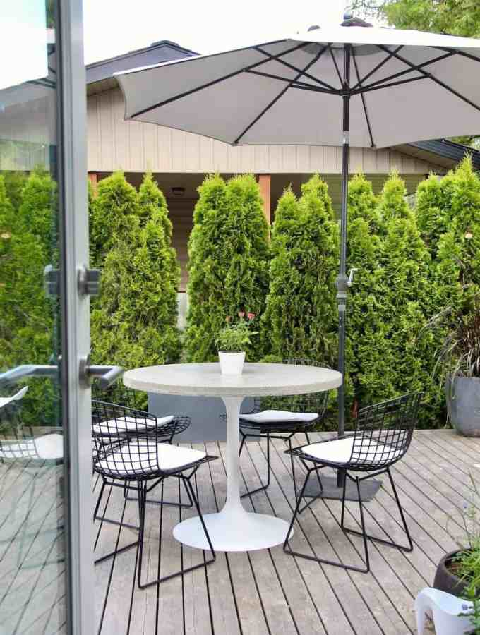modern patio furniture on grey wooden deck with glass door and umbrella