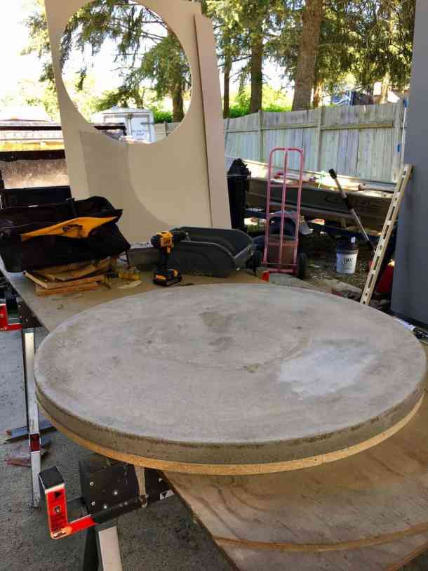 Round poured concrete table top on outside workbench surrounded by tools