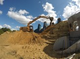The excavator is sitting on a ramp made by the bulldozer so it could reach high enough to place the dirt.