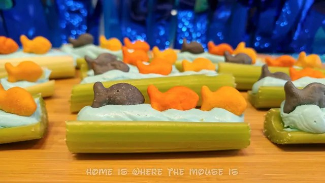 Goldfish swim a top celery sticks lined with blue cream cheese.