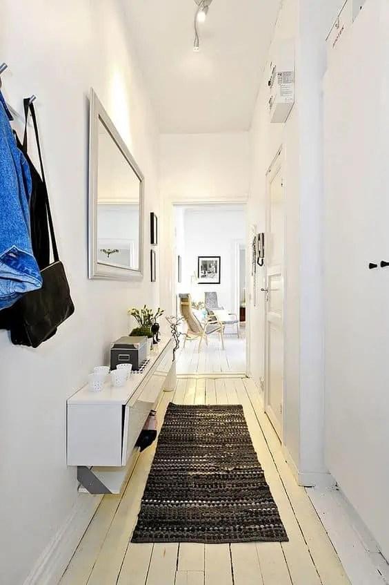 un couloir avec les murs peints en blanc et un tapis noir pour habiller et contraster