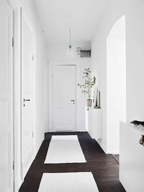 couloir avec un sol fonce noir et une peinture blanche pour les murs contraste assure