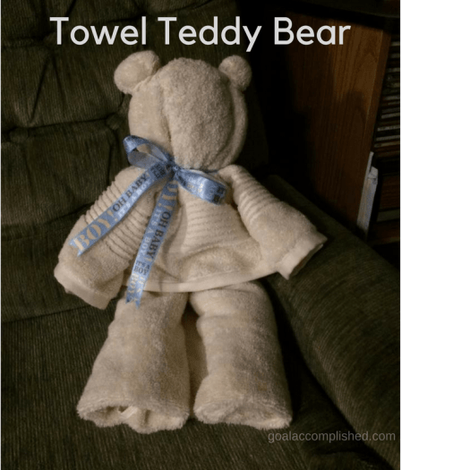 "Towel teddy bear sitting in chair with blue ""Boy"" ribbon around neck"