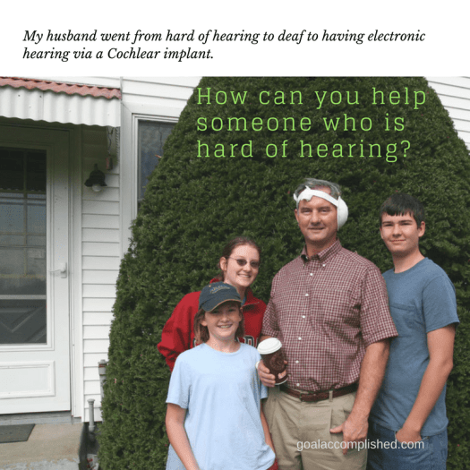 Hearing impaired Man with bandage on left ear standing with 3 kids