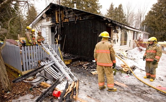 Firefighters clean up debris after fire razed a Hargrave Rd. home east of Kirkfield on Friday, Mar. 18, 2011.