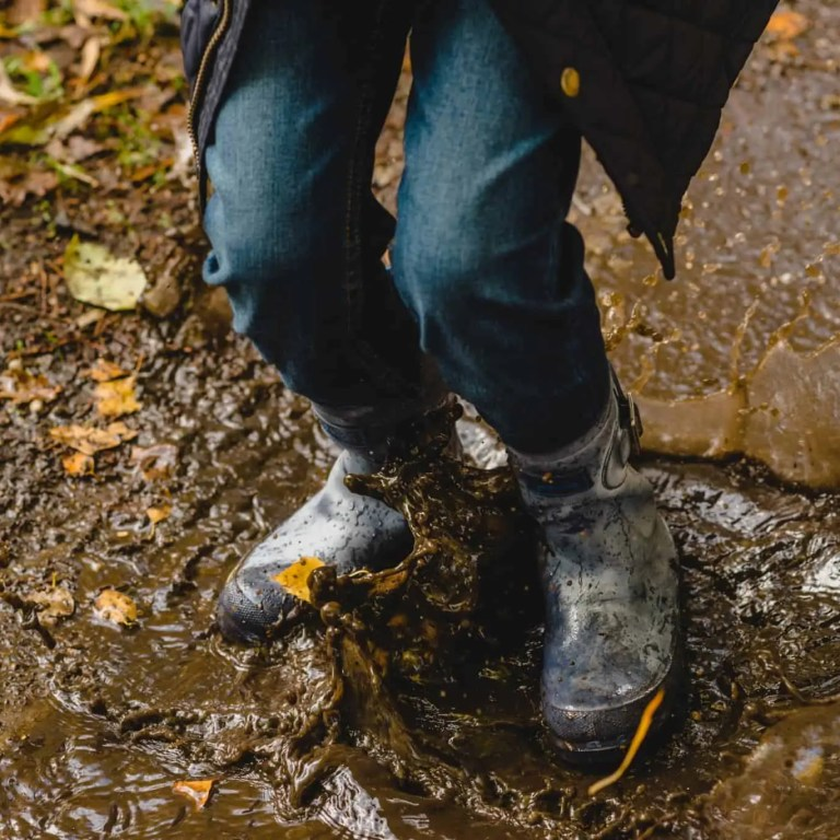 Kids jumping in a muddy puddle with wellies