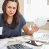 Young woman getting stressed over finances in kitchen