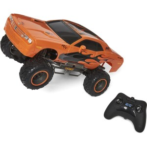 Orange toy car next to remote control, pointing to the left corner