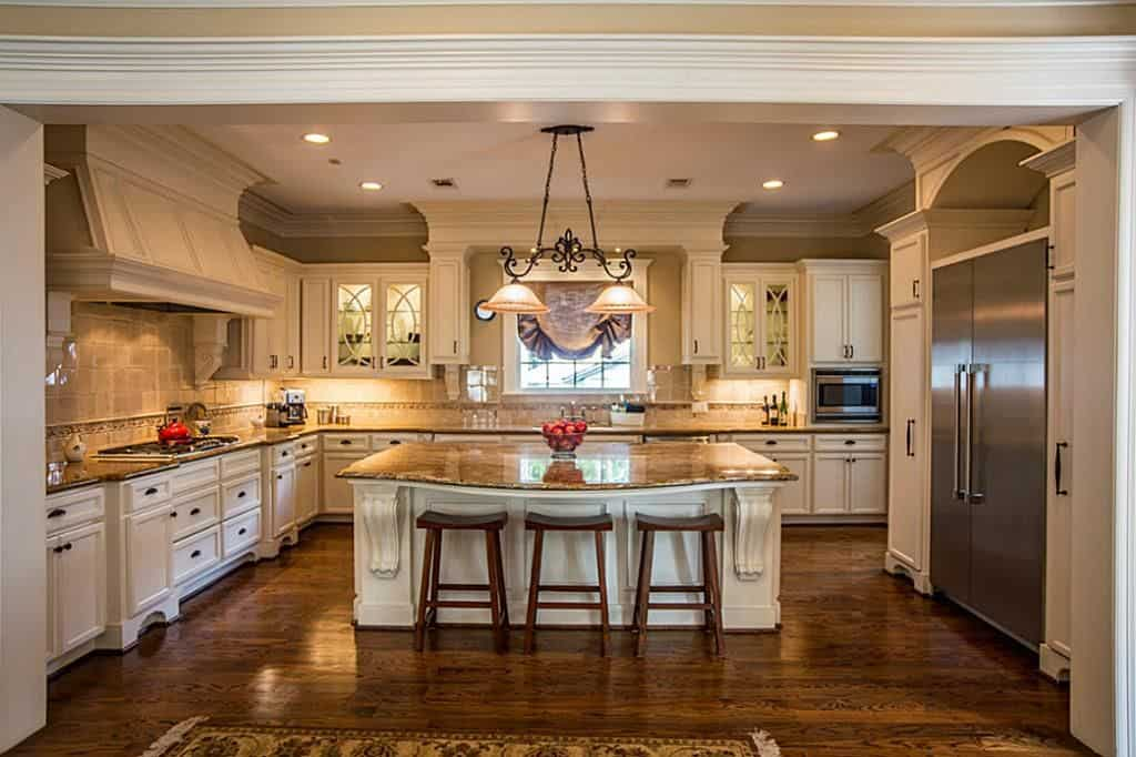30 Custom Luxury Kitchen Designs that Cost More than  100 000 White traditional luxury kitchen with rich wood flooring inu shape with  center island