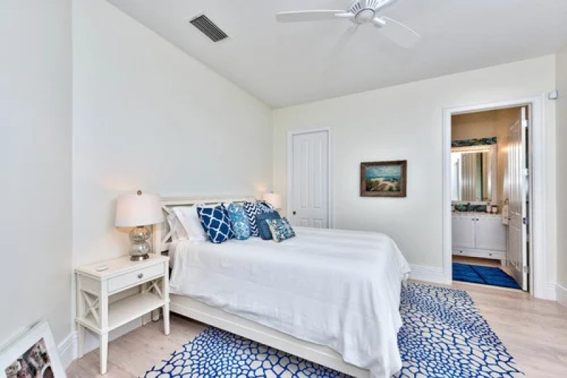 A combination of blue accent pieces and light wooden flooring in a whitewashed master bedroom achieves a beach-style appeal. Photo by Palm Brothers Remodeling