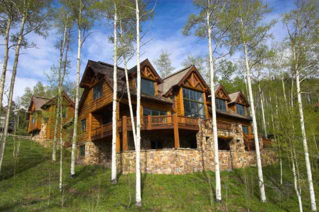 Grand log home with huge windows and large deck on stone foundation set among tall trees.