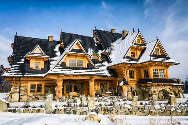 Rambling mega log home mansion with light wood logs and dark shingle roof for contrast effect. Snow on the ground.