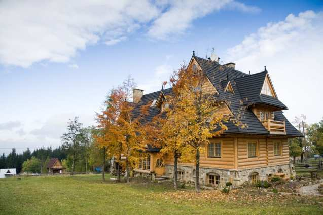 Beautiful light wood log home with steeply pitched roof on large property.