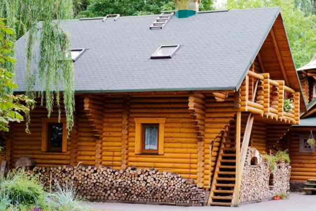 Cozy log home with upper deck and plenty of firewood storage on side and front.