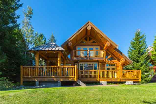 Stylish custom log home with full width sun deck and natural colored logs set on grass property.