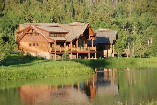 Large custom log home built on lake front set against mountains.