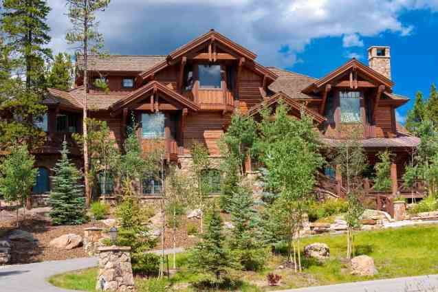 Contemporary log home mansion on sloping property built with dark logs (and stained).
